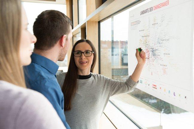 """Studierende stehen an einer Karte mit Titel """"Landkarte der Changemaker"""""""