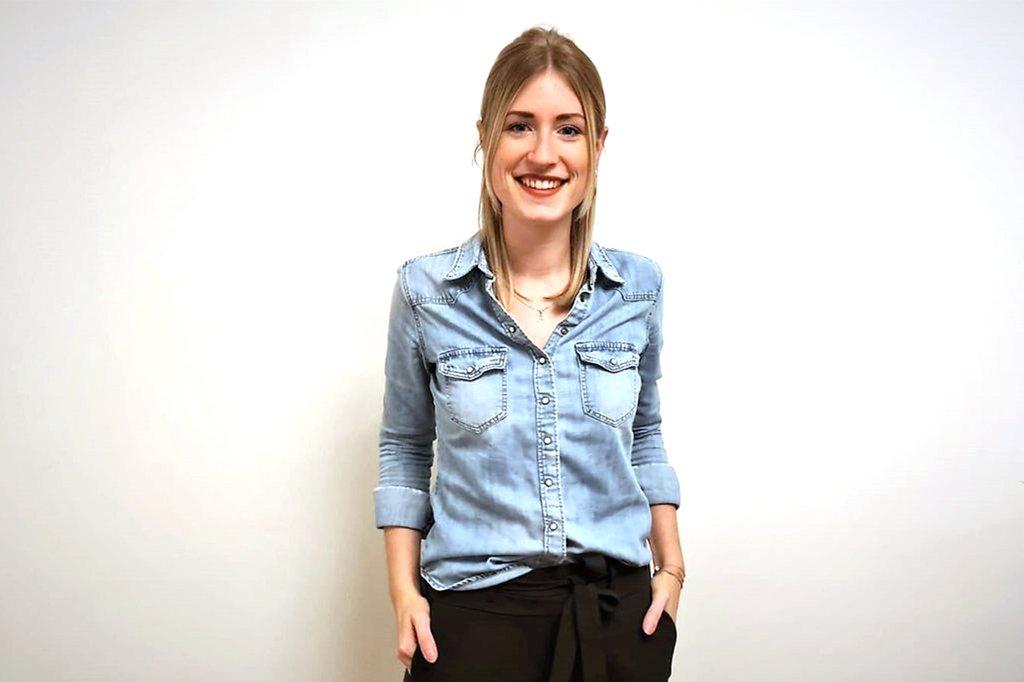 Anna Lienhart lehnt an einer Wand und lächelt in die Kamera