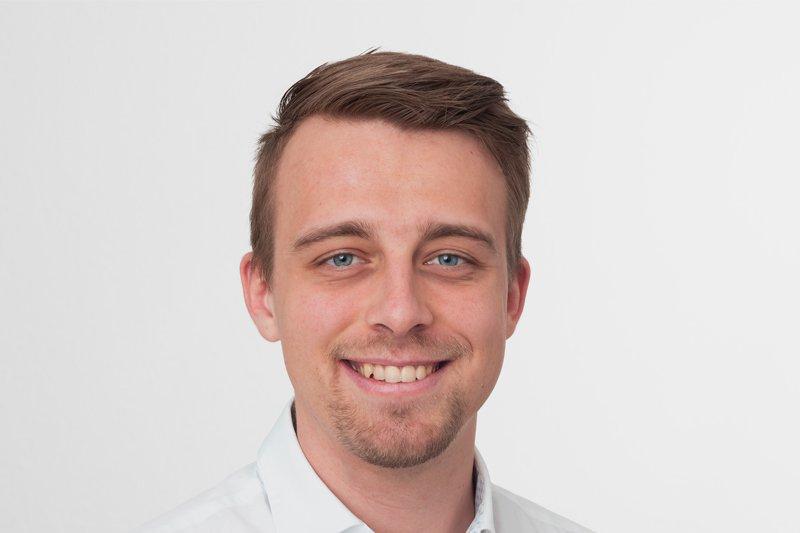 Porträt des FH St. Pölten-Alumni Lukas Snizek – er lächelt in die Kamera und trägt ein weißes Hemd