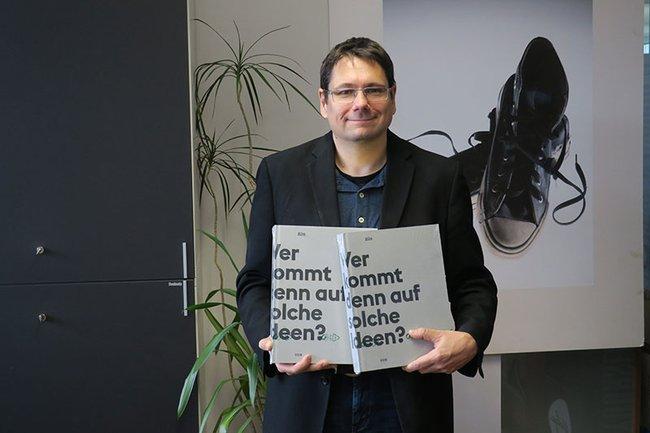 Helmut Kammerzelt, Studiengangsleiter Media- und Kommunikationsberatung, mit zwei Exemplaren der vom Creativ Club Austria geschenkten Bücher.