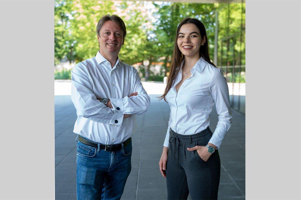Links im Bild: Alexander Adrowitzer, Rechts: Laura Kaltenbrunner - beide stehen vor dem Hauptgebäude der FH, im Hintergrund sind Bäume sichtbar