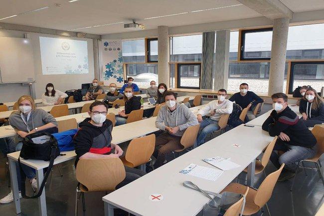 Die Teilnehmen des Kurses sitzen - mit FFP2 Masken und Abstand - im Seminarraum und schauen in die Kamera