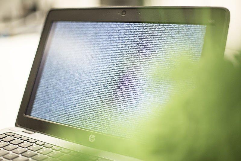Symboldbild: Laptop mit Code auf dem Bildschirm