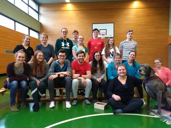 Studierende des 1. Semesters (Bachelor Studiengang Physiotherapie) mit Physiotherapeutin Cornelia Rottensteiner und Therapiehündin Fini