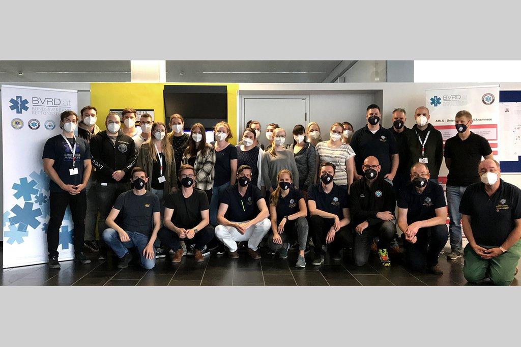 Gruppenfoto der Studierenden und Lehrenden des notfallmedizinischen Spezialkurses in einem Seminarraum neben Aufstellern des BVRD (Bundesverband Rettungsdienst) – alle tragen FFP2 Masken