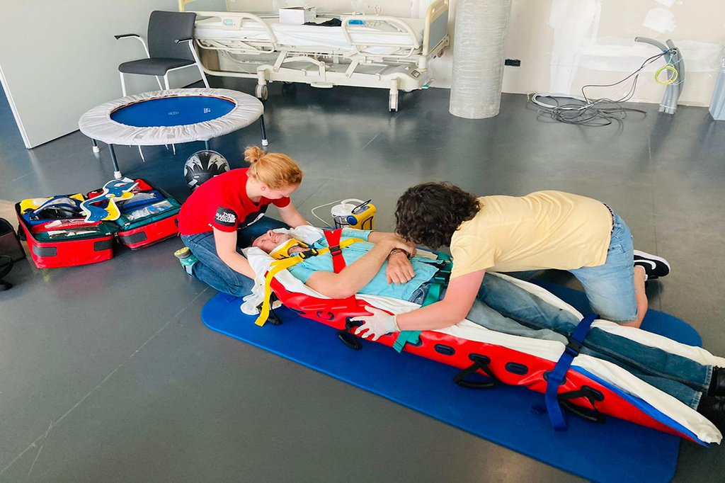 Auf dem Bild sieht man Stefan Rottensteiner in einer Rettungstrage am Boden liegen. Daneben sind zwei Studentinnen, die ihn verarzten.