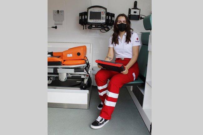Die junge Studierende Anna Reisner sitzt im Rettungswagen, sie trägt die Uniform des Österreichischen Roten Kreuzes und eine schwarze FFP2 Maske