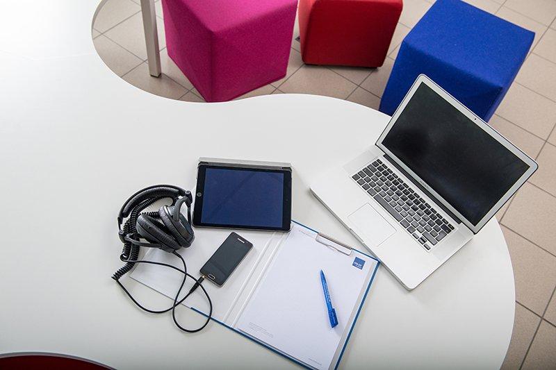 Auf einem Tisch liegen ein Laptop, ein Handy, ein Tablet, ein Kopfhörer und ein Notizbuch - hinter dem Tisch stehen Sitzwürfel