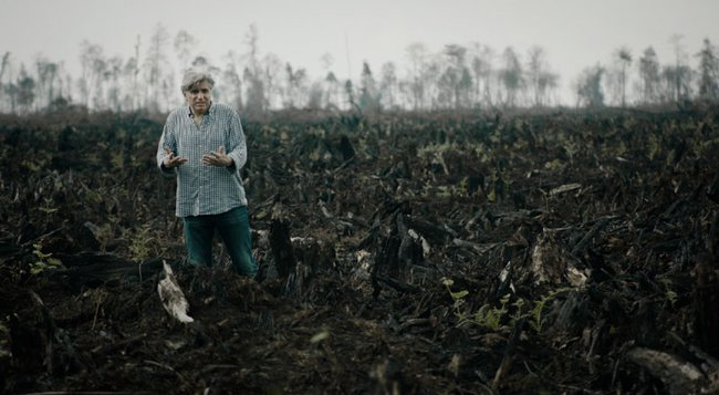 Werner Boote inmitten eines verbrannten Feldes beim Filmdreh