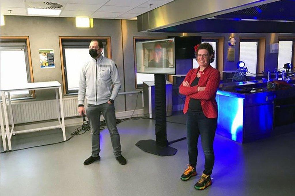 2 Vortragende, ein Mann und eine Frau, stehen seitlich vor einem Screen. Der Mann trägt eine FFP2 Maske und hält ein Mikrofon