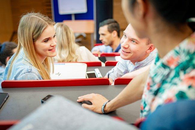 Im Hörsaal sind mehrere Studierende sichtbar, die fröhlich auf ihre nächste Vorlesung warten