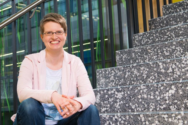Kerstin Blumenstein sits on the stair of the main building of St. Pölten UAS and smiles into the camera